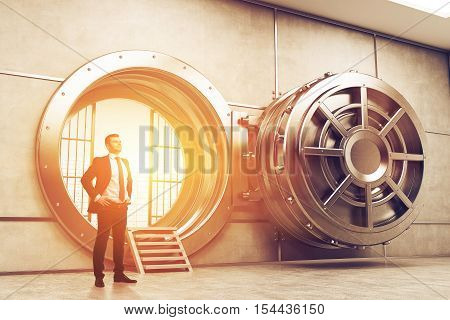 Confident businessman is standing near wide open vault door. Concept of money saving. 3d rendering. Toned image