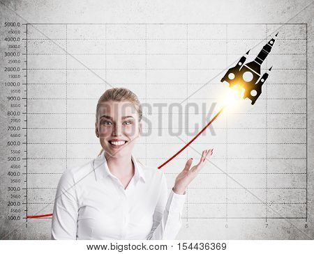 Smiling blond woman is standing near concrete wall and showing a graph and a rocket sketch. Concept of growing business.