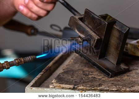 Close-up of Goldsmith using Blowtorch on Metal Mold in order to melting Metal; Goldsmith Workshop