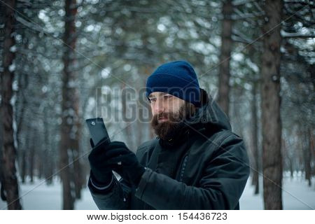Handsome bearded man makes selfie in forest in winter. Happy bearded young man talking on mobile phone outdoors in winter