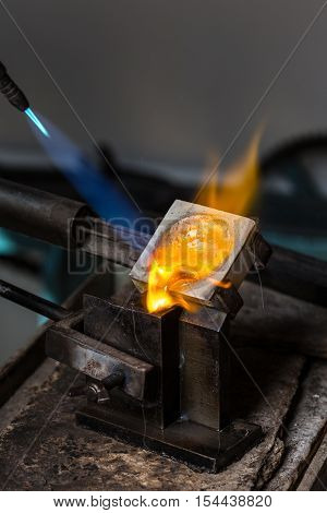 Close-up of Silver Casting from Crucible to Metal Mold with blowtorch; Goldsmith Workshop;