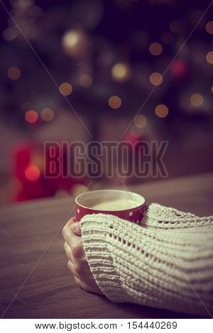 Close up of female hands holding a cup of hot coffee with the Christmas tree and presents in the background. Selective focus