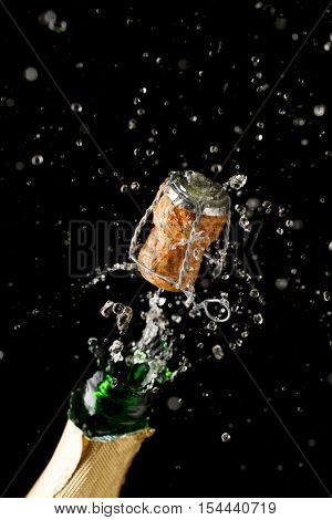 Opening bottle of champagne on empty black background