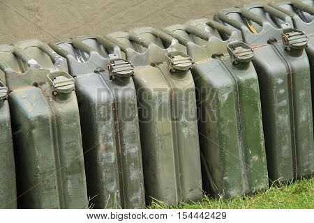 A Line of Vintage Military Metal Petrol Fuel Cans.