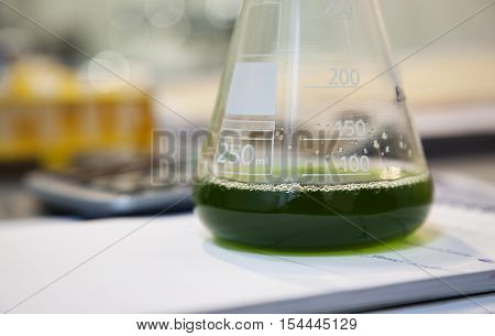 Close-up of a flask with green solution in a laboratory