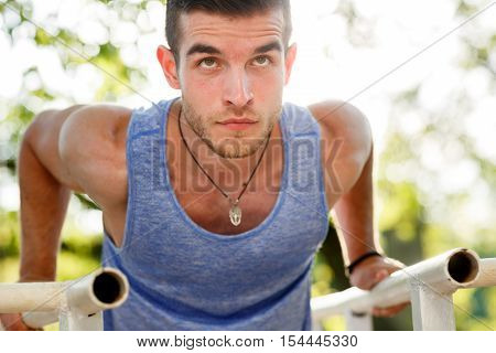 Closeup portrait of sports man doing pull-ups on parallel crossbars on nature