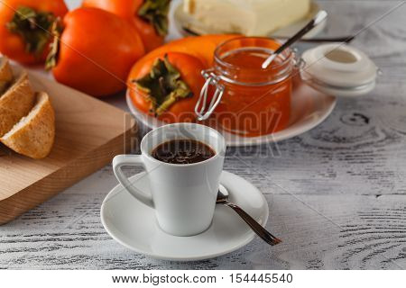 persimmon fruit jam on wooden table with coffee cup