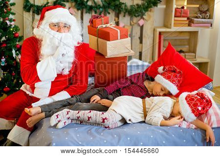 Santa Claus quietly came to the children who are sleeping lying on decorated bed with Christmas tree in the background