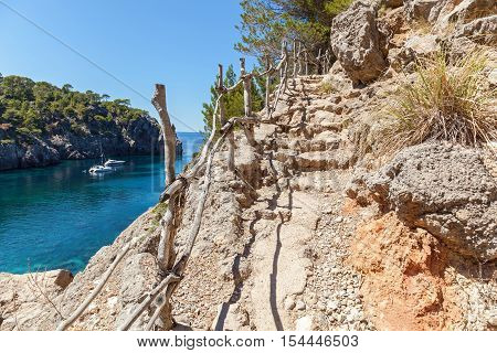 Stairs on the mountain. Beautiful view of Mallorca coast from the high of the cliff wooden handrail and blue sea.