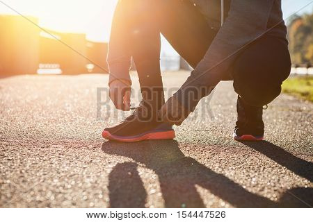 Man tying jogging shoes on sunset. Lifestyle concept