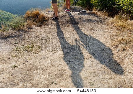 Shadow of two people holding hands on a hill with the sun-scorched grass