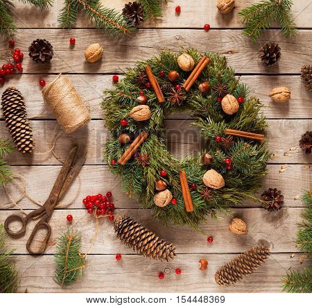 Advent Christmas wreath decoration with natural decorations, pine cones spruce, nuts, candied fruit on wooden rustic background. Christmas decorations.