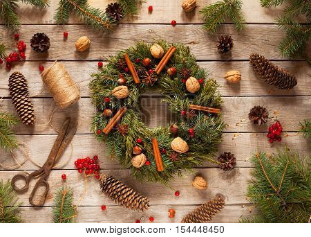 Advent Christmas wreath with natural decorations, pine cones spruce, nuts, candied fruit, cinnamon on wooden rustic background. Christmas decorations.