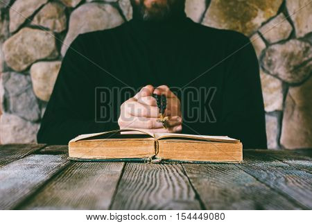 a man in black clothes with a prayer beads in hand praying in front of an old open book. the concept of praying and studying. selective focus