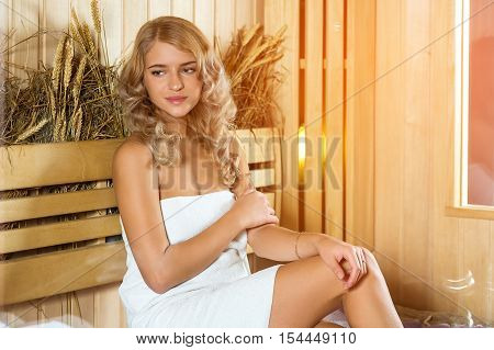 Young beautiful woman relaxing in the Finnish sauna wrapped in towel