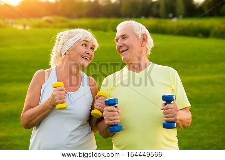 Smiling couple with dumbbells. Old man and woman outdoor. Light training program for pensioners. Many years in sport.
