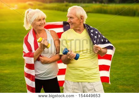 Senior couple holds dumbbells. Couple wrapped in US flag. Nation of the fittest. Victories and pride.