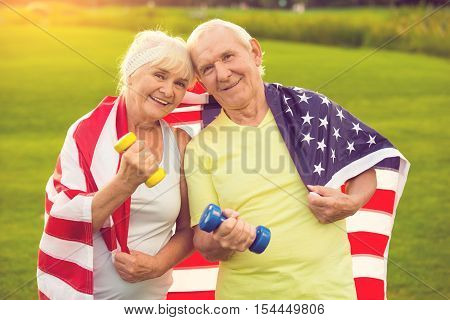 Couple of seniors with dumbbells. People with USA flag. Stay true to family values. Health and patriotism.