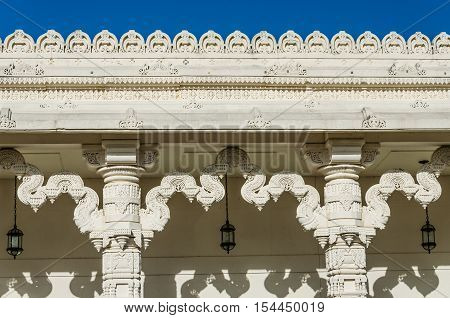 Detailed ornament on the wall of a Hindu temple with columns.