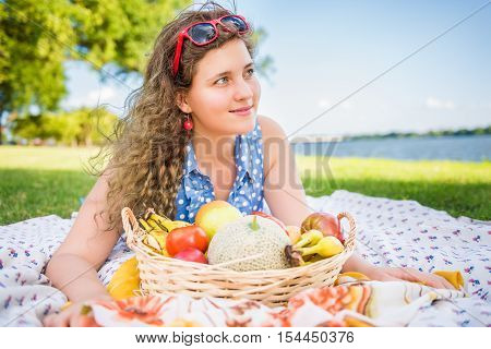 Young woman lying down and smiling looking away on picnic blanket with fruit basket near Potomac River in Washington, DC