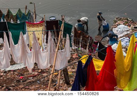 DHAKA BANGLADESH- DECEMBER 30 2016. Unidentified washerman wash their cloths in the river