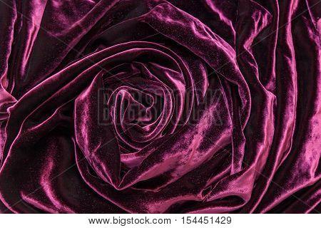 Vinous silk velvet. Vinous silk velvet fabric twisted in form of the rose.
