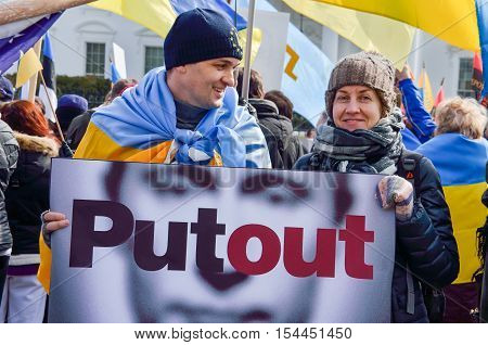 Washington DC, USA - March 6, 2014: Man and woman holding Vladimir Putin sign stating Putout during Ukrainian protest with flags by White House