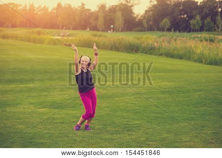 Woman in headphones dancing. Senior lady on grass background. Open your mind to music. World famous hits.