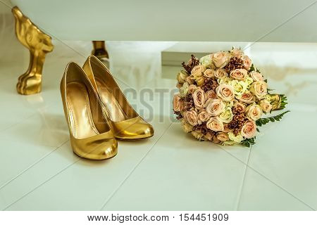 Golden shoes. Close up of the wedding golden female shoes and bouquet of flowers on the white tile in bathroom.