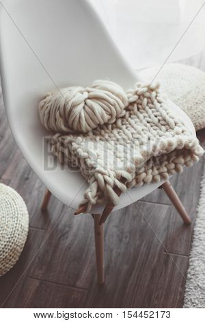Thick yarn and wooden needles on modern plastic chair in living room, top view. Chunky knit. Details of white scandinavian interior.