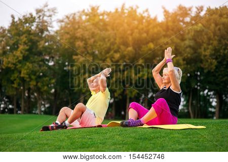 Couple doing yoga outdoor. Elderly people sitting on mats. Sense of harmony. Meditation in open air.
