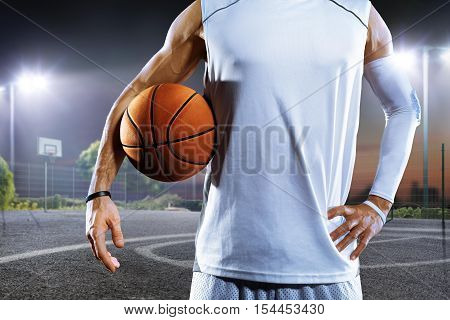 Streetball player holding ball on grand arena