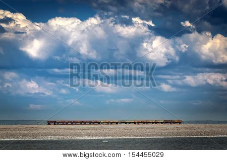 Several railroad hopper cars parked on rural tracks all by themselves on a hot Spring day. Few old carriages left alone on a railroad among beautiful nature. Blue sky and big white clouds surround train