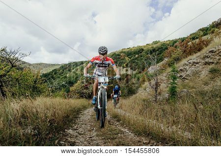 Privetnoye Russia - September 22 2016: two riders cyclists riding uphill on a background of mountains and clouds during Crimean race mountainbike