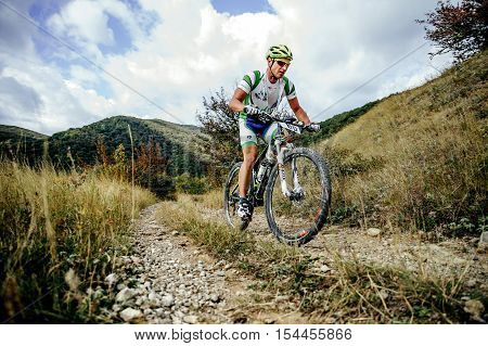 Privetnoye Russia - September 22 2016: male rider cyclist riding uphill on a background of mountains and clouds during Crimean race mountainbike