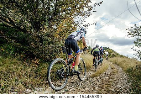 Privetnoye Russia - September 22 2016: group of riders cyclists riding uphill one behind other during Crimean race mountainbike