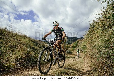 Privetnoye Russia - September 22 2016: racer mountainbiker rides on a mountain trail smile on face during Crimean race mountainbike