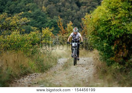 Privetnoye Russia - September 22 2016: female rider cyclist riding uphill among woods and grass during Crimean race mountainbike
