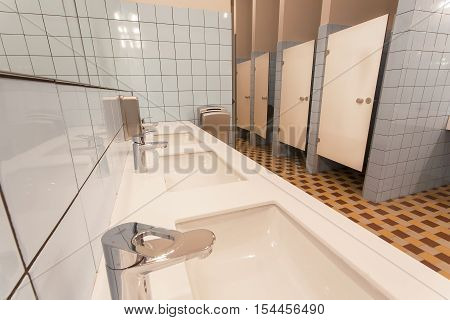 Several washbasin and seperated toilet cabins in huge bathroom of a youth hostel