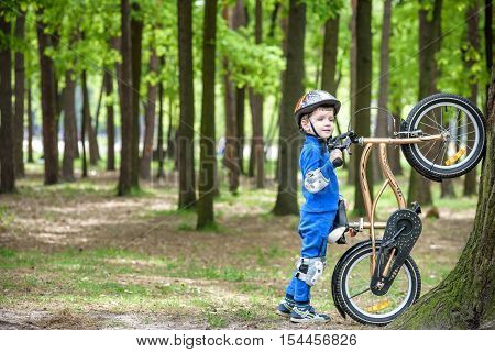 Happy Kid Boy Of 4 Years Having Fun In Autumn Or Summer Forest With A Bicycle