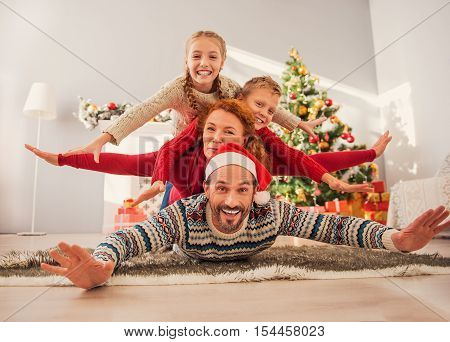 This is our favorite Christmas. Happy children and woman are lying on father with joy. They are stretching arms sideways and laughing