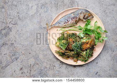 Fried Acacia Pennata Climbing Wattle with egg and fried mackerel on wood plate (cha-om kai in Thai)