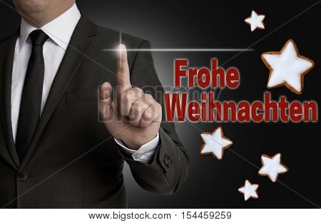Frohe Weihnachten (in german Merry Christmas) touchscreen is operated by a businessman.