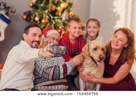 Friendly family is making selfie on smartphone and smiling. They are sitting near Christmas tree and embracing dog