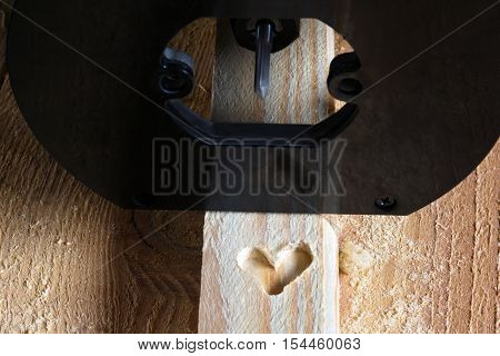 shape of heart carved on a wooden batten by milling cutter
