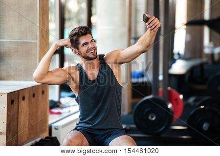 Young fitness man makes selfie in gym