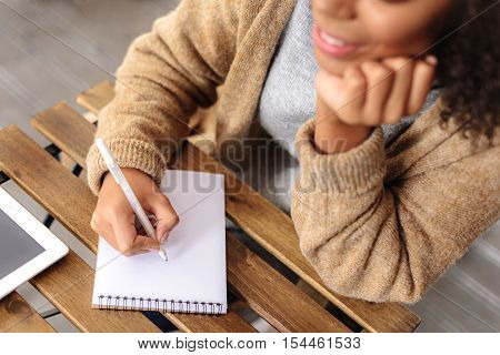 hand of a woman drawing in a jotter on the table, selective focus