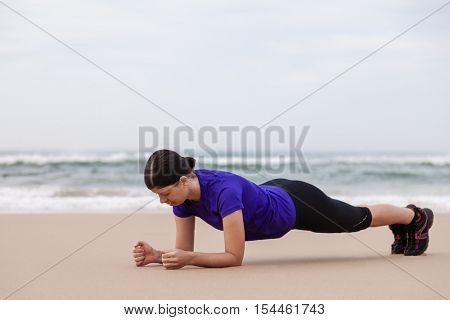 Female athlete executing the plank exercise at the beach on an Autumn day.
