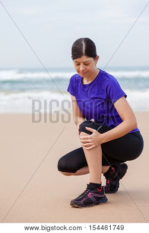 Female athlete suffering from a knee injury at the beach on an Autumn day.