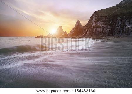 Stunning Dramatic Sunrise Over Beach With Jagged Rocks Coastline